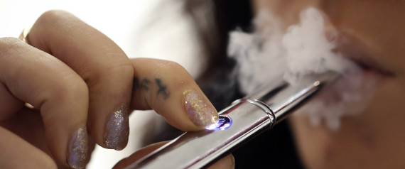 An employee poses for a photograph smoking a V-Revolution e-cigarette inside the company's store in London, U.K., on Wednesday, Oct. 16, 2013. The U.S. Food and Drug Administration is set to decide this month whether to lump e-cigarettes in with conventional smokes as part of its oversight of the $90 billion U.S. tobacco market. Photographer: Chris Ratcliffe/Bloomberg via Getty Images