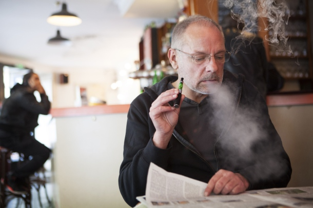 Man with an electronic cigarette in a public place.